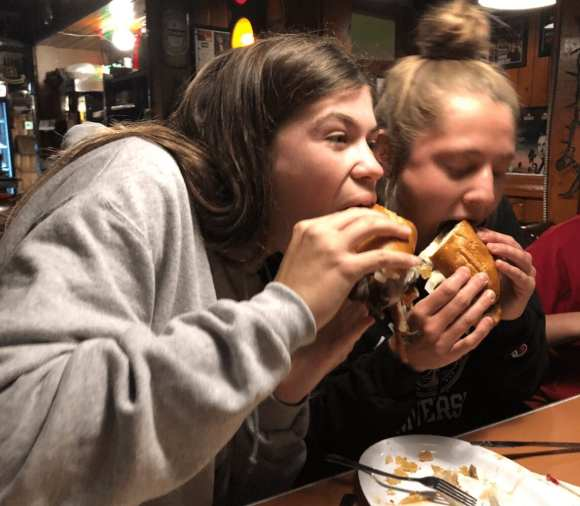 Hannah (left) and Kirsten try a Philly cheese steak at the Harbor House.